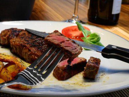 angeschnittenes Steak auf Teller, mit Gemüsegarnitur