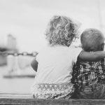 Schüßler Salze für Babys und Kleinkinder, hier zu sehen Geschwister von hinten, auf einer Bank sitzend, das Ältere legt den Arm um das Jüngere