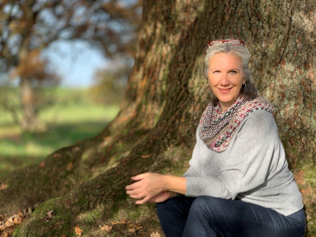 freundliche Frau in der Herbst-Sonne unter einem Baum