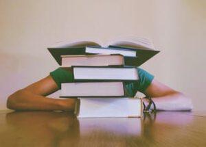 Schreibtisch mit Student, der sich hinter Bücherstapel verkriecht