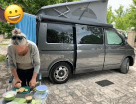vor grauem VW Bus steht Frau in gebeugter Haltung und macht Essen
