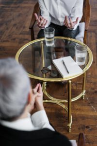 zwei Menschen an einem kleinen runden Tisch im Gespräch