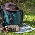 Erholung, Pause für Kiefer und Körper auf einer Wanderung: Rucksack und Wanderstiefel auf einer sonnigen Wiese
